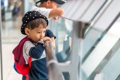 Il ragazzino asiatico 3 anni porta l'imbarco aspettante della borsa al volo nel corridoio terminale di transito dell'aeroporto de immagine stock libera da diritti