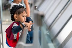Il ragazzino asiatico 3 anni porta l'imbarco aspettante della borsa al volo nel corridoio terminale di transito dell'aeroporto de fotografia stock