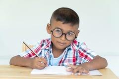 il ragazzino asiatico scrive il compito fotografia stock libera da diritti