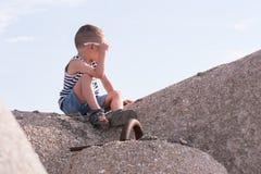 Il ragazzino in buona salute in occhiali da sole e maglia si siede su un frangiflutti che guarda da parte Fotografia Stock Libera da Diritti