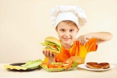Il ragazzino in cappello dei cuochi unici espressivo gode dell'hamburger cucinato Immagine Stock