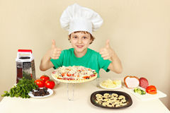 Il ragazzino in cappello dei cuochi unici gode di di cucinare la pizza Immagine Stock