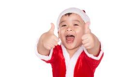 Il ragazzino in cappello di Santa con i pollici aumenta il segno, su bianco Fotografie Stock