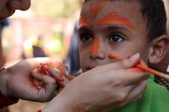 Il ragazzino che ha suo fronte ha dipinto i bambini divertendosi il gioco fotografia stock