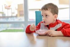 Il ragazzino che mangia il jogurt alla frutta in una ciotola Fotografie Stock Libere da Diritti