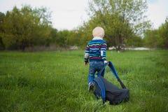 Il ragazzino con capelli biondi che tirano un grande chery dello zaino sull'erba verde in natura, viaggio, bambino, avventura Fotografia Stock