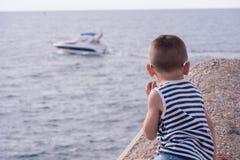 Il ragazzino con gli occhiali da sole e la maglietta giro collo a strisce esamina il mare con la barca di galleggiamento Fotografie Stock
