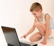 Il ragazzino con il computer portatile Immagini Stock Libere da Diritti