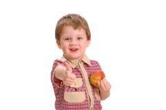 Il ragazzino con il pollice alto e la mela Immagine Stock