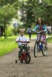Il ragazzino con il suo giro della sorella bikes nel parco Camminata Immagine Stock