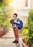 Il ragazzino con la borsa di scuola legge il libro sulla via Immagine Stock Libera da Diritti