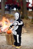 Il ragazzino in costume di scheletro spaventoso su fondo del falò alle celebrazioni di Halloween fa festa in foresta fotografie stock libere da diritti