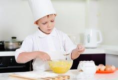 Il ragazzino in cuochi unici uniforma la cottura nella cucina Fotografie Stock