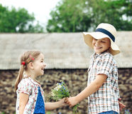 Il ragazzino dà i fiori alla bambina Fotografia Stock