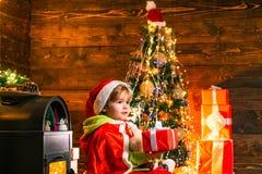Il ragazzino delle curiosità sta giocando con i giocattoli dall'albero di Natale Il bambino sta indossando i vestiti di Santa Con immagini stock libere da diritti