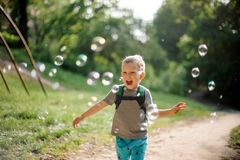 Il ragazzino di risata con le bolle di sapone di estate parcheggia sul da soleggiato Fotografia Stock
