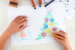 Il ragazzino disegna un albero del nuovo anno Il bambino gradisce disegnare un albero di Natale immagini stock