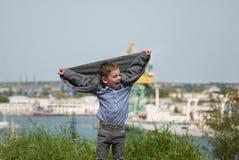 Il ragazzino divertente ha sollevato le sue mani su con il suo rivestimento Fotografie Stock Libere da Diritti