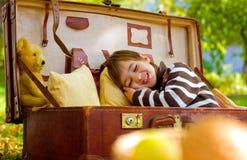Il ragazzino dorme in una grande valigia nel parco di autunno Fotografia Stock