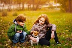 Il ragazzino e la ragazza con il suo cucciolo sollevano russell con il crick in outdoo di autunno immagini stock libere da diritti