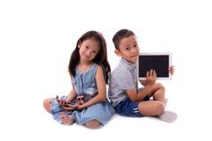 Il ragazzino e la ragazza godono di di giocare ed imparare con lo smartphone o l'aggeggio di Internet che si siede sul pavimento  Fotografia Stock