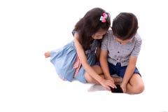 Il ragazzino e la ragazza godono di di giocare ed imparare con lo smartphone o l'aggeggio di Internet che si siede sul pavimento  immagine stock