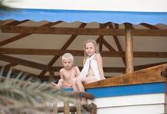 Il ragazzino e la ragazza si siedono su un contatore di legno Immagini Stock