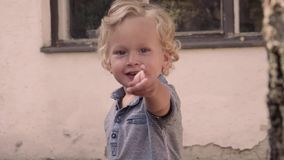 Il ragazzino esamina la macchina fotografica ed il dito indicare video d archivio