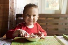Il ragazzino esamina la macchina fotografica mentre mangia la prima colazione immagine stock