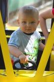 Il ragazzino esamina la macchina fotografica mentre tiene la rotella Fotografia Stock