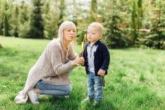 Il ragazzino fa le bolle con sua madre al parco Fotografie Stock