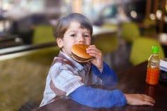 Il ragazzino in fast food mangia l'hamburger fotografia stock libera da diritti