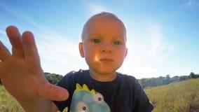 Il ragazzino felice che guarda nella macchina fotografica e la tocca all'aperto Il bambino sveglio tocca la lente della videocame Immagine Stock
