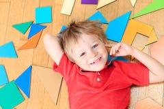 Il ragazzino felice con il puzzle gioca sul pavimento di legno Immagine Stock