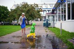 Il ragazzino felice nell'non ottenere i vestiti bagnati gioca in stagno sulla via con la nonna Fotografia Stock Libera da Diritti