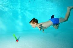 Il ragazzino felice si tuffa per un giocattolo sotto l'acqua nello stagno e sorride Fotografia Stock