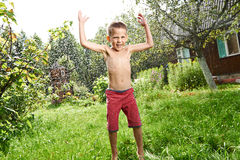 Il ragazzino felice sta saltando sotto pioggia Fotografia Stock Libera da Diritti