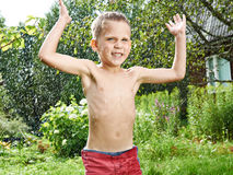 Il ragazzino felice sta saltando sotto pioggia Fotografie Stock Libere da Diritti