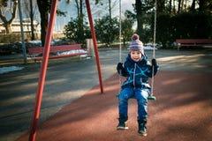 Il ragazzino felice su oscillazione nel bello giorno di inverno si diverte e fa i fronti Fotografia Stock