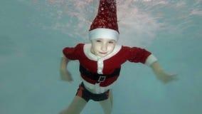 Il ragazzino felice in un vestito rosso Santa Claus nuota underwater nello stagno nei getti di acqua, sorridenti e esaminare la m archivi video