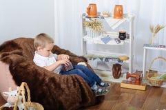 Il ragazzino gioca con i fagioli che si siedono su una sedia della pelliccia La stanza con una decorazione rustica Fotografia Stock Libera da Diritti