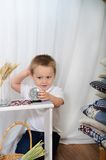 Il ragazzino gioca l'orologio da tavolino La stanza con una decorazione rustica Fotografia Stock Libera da Diritti