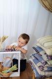 Il ragazzino gioca l'orologio da tavolino La stanza con una decorazione rustica Fotografia Stock