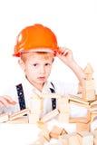 Il ragazzino impila la casa dall'isolato di legno dei blocchi Fotografia Stock Libera da Diritti