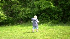 Il ragazzino intraprende i suoi primi punti su erba fresca nel parco della città video d archivio