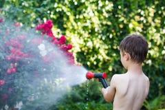 Il ragazzino irriga in giardino Immagine Stock