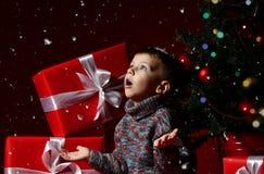 Il ragazzino la vigilia del nuovo anno e del natale sta sedendosi sotto l'albero immagine stock libera da diritti