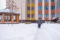 Il ragazzino libera i percorsi della pala nell'iarda da neve immagini stock