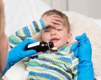 Il ragazzino malato attende il suo farmaco che versa in un cucchiaio immagini stock