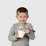 Il ragazzino mangia il yogurt su gray Immagine Stock Libera da Diritti